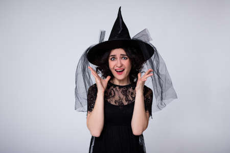 halloween concept - portrait of beautiful screaming woman in black witch halloween costume and hat over white background with copy space 版權商用圖片