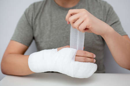 fracture and first aid concept - man bandaging his hand