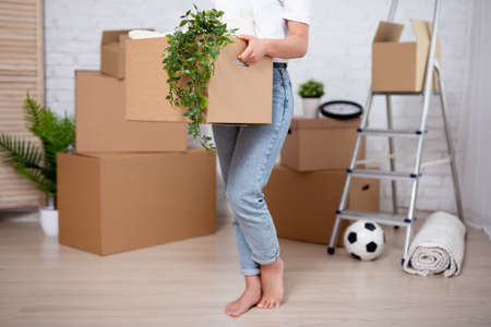 young woman with cardboard boxes ready to move in new house