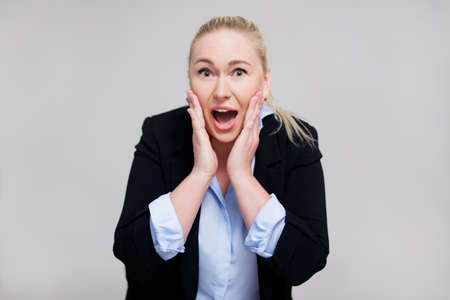 announcement or advertisement concept - surprised blonde woman screaming about something over gray background