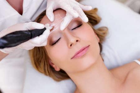 concept de maquillage et de beauté - gros plan d'une esthéticienne appliquant un maquillage permanent sur les sourcils