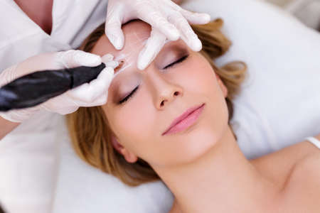 Make-up- und Beauty-Konzept - Nahaufnahme einer Kosmetikerin, die Permanent Make-up auf die Augenbrauen aufträgt