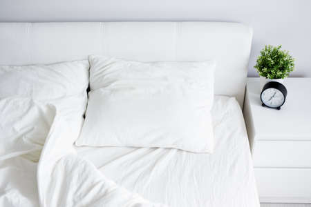 top view of empty unmade bed with white blanket and two pillows, bedside table with alarm clock and home plant pot at home or hotel