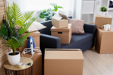 moving day concept - stack of brown cardboard boxes with belongings in new house