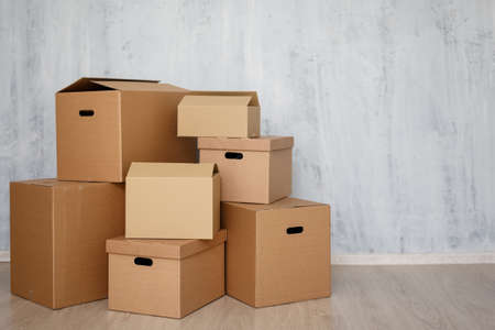 moving day or postal delivery concept - brown cardboard boxes stacked on the floor and copy space over gray wall background Reklamní fotografie