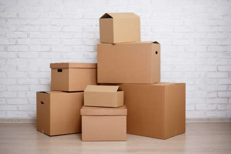 cardboard boxes over white brick wall background