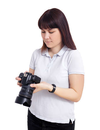 portrait of young attractive female photographer posing with camera in her studio