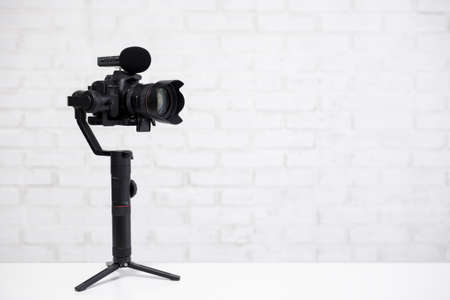 full length portrait of professional videographer with dslr camera on 3-axis gimbal isolated on white background