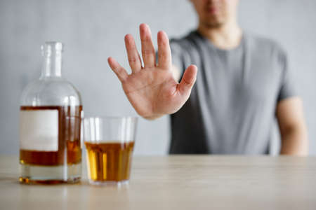 alcoholism concept - young man refusing glass of whiskey with open palm gesture