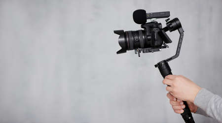 modern dslr camera on 3-axis gimbal stabilizer with follow focus system in male videographer hands over gray background with copy space