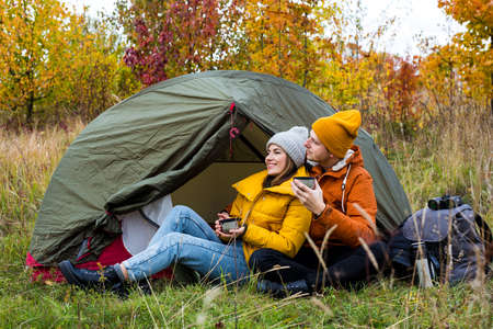 travel, trekking and hiking concept - cute couple drinking tea or coffee near green tent in autumn forest Standard-Bild