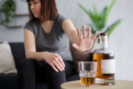 alcoholism concept - young woman refusing glass of whiskey with palm gesture