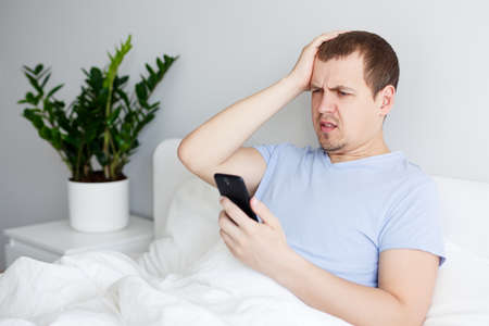 portrait of young upset man using smartphone in bed
