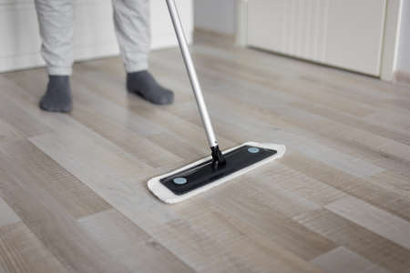 housekeeping concept - close up of cleaning wooden parquet floor with mop