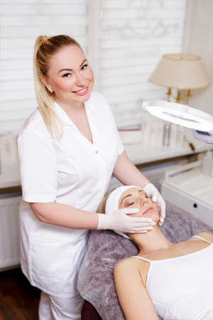 cosmetology and plastic surgery concept - portrait of female cosmetologist and young woman in beauty spa salon