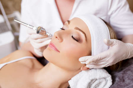 cosmetology and beauty concept - close up portrait of woman getting facial oxygen anti-aging procedure in beauty salon