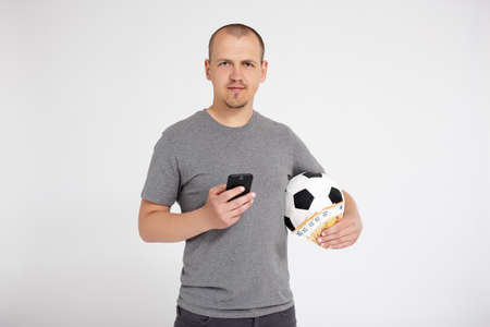 sport, online bet, success, win and money concept - portrait of young man using smart phone and holding euro money and soccer ball over grey background with copy space