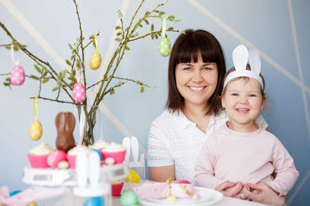 Family, happiness and spring holidays concept - portrait of happy mother with cute little daughter and decorated table with cream cupcakes and colorful painted Easter eggs