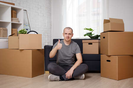 moving day - hadsome man sitting on floor in his apartment with moving boxes and thumbing up