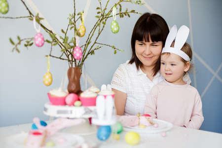Family and Easter concept - happy mother with cute little daughter and decorated table with cream cupcakes and colorful painted Easter eggs