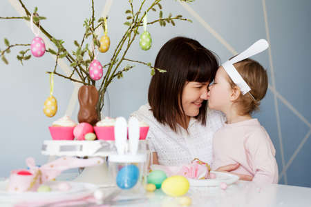 Family and Easter concept - happy mother with cute little daughter and decorated table pussy willow branch with cupcakes, colorful painted Easter eggs and decorations