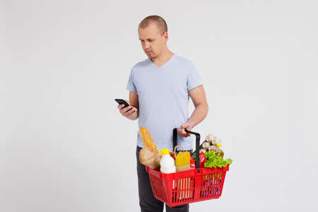 online shopping concept - portrait of young man with shopping basket full of products using smart phone over white background Stock fotó