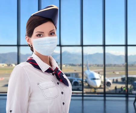 pandemic, vacation and travel concept - portrait of beautiful stewardess in medical mask posing in airport