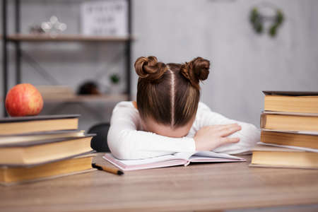 school, homework and education concept - bored, stressed or tired cute school girl doing homework with heap of books at home