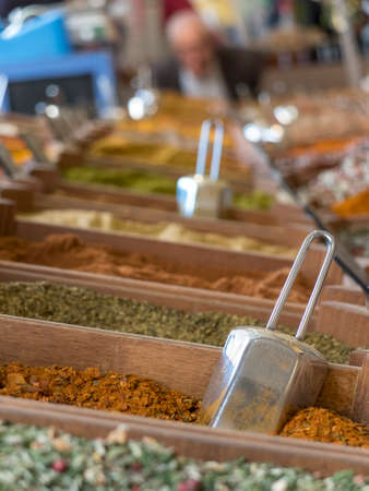 small wooden crates with various types of minced spices and grains: curcuma, curry, cajun, keufta, paprika and various infusions.