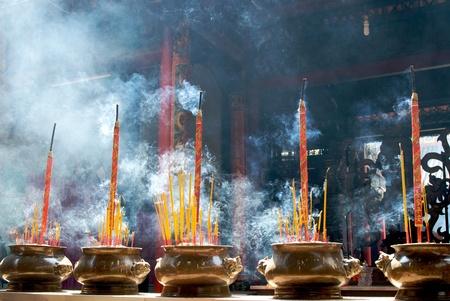 Smoking prayer sticks in copper urns. Thien Hau Pagoda, Ho Chi Minh, Vietnam.  photo