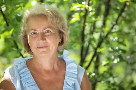 Smiling senior woman outdoor in a park Stock Photo