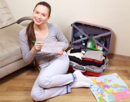 Young woman packing a suitcase at home going on holiday photo