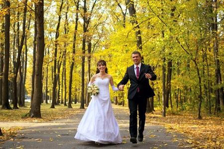 Bruid en bruidegom lopen in een park