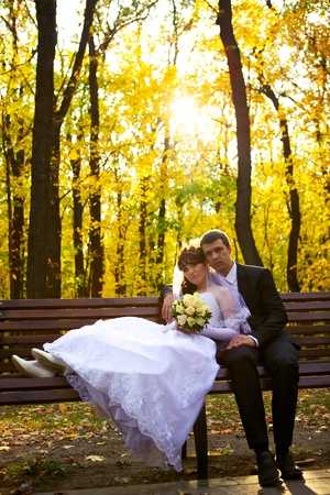 Bride and Groom sitting on a bench in a park  photo