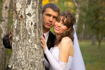 Bride and Groom standing near tree in a park  photo