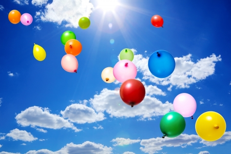 Color flying balloons in blue sky with clouds and sun Stock Photo