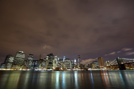 Nighttime view of Lower Manhattan skyline with Brooklyn Bridge in New York City photo