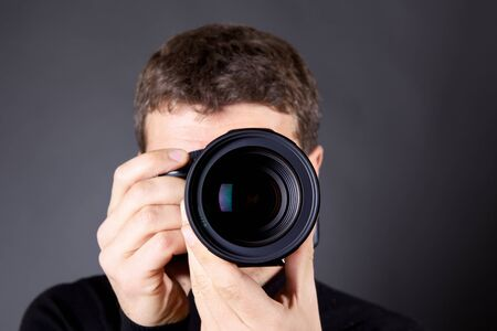 photojournalist: Photographer with a camera, focus is on the lens