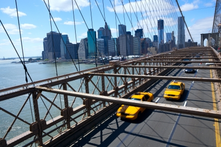 New York Manhattan skyline from the Brooklyn Bridge with yellow taxis Stock Photo