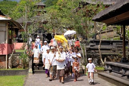 procession: BALI - OKTOBER 17, 2011 gente de Bali que caminan en vestido tradtional en el cortejo f�nebre, Besakih complejo en Bali, Indonesia