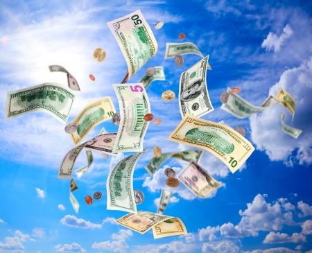 dinero volando: Billetes de dólares americanos y monedas cayendo desde el cielo azul