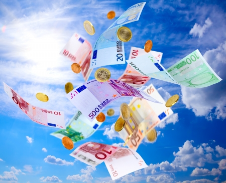 dinero volando: Los billetes y monedas cayendo del cielo azul