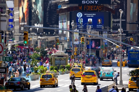New York, New York, USA - July 6, 2012: Times Square with busy traffic, yellow taxi and crowds of people in a sunny day, Midtown Manhattan