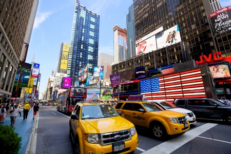 New York, New York, USA - July 11, 2012: Yellow taxis on 7th Avenue in Times Square with crowds of people and lots of advertising