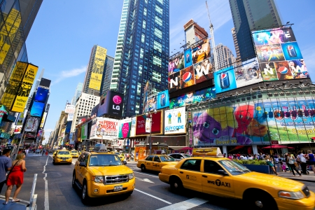 New York, New York, USA - July 11, 2012: Yellow taxi cabs crossing Times Square with crowds of people and lots of advertising in a sunny day
