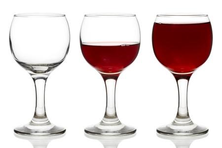 half and half: Tres vasos vac�os, medio y lleno de vino rojo aislado en blanco Foto de archivo