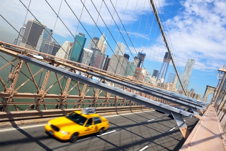 Taxi cab crossing the Brooklyn Bridge in New York, Manhattan skyline in background Stok Fotoğraf