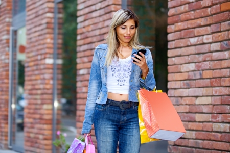 Woman with shopping bags and cellphone walking on street photo