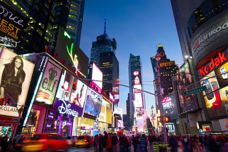 busy street: New York, New York, USA - December 15, 2012: Cars and taxis on 7th Avenue in Times Square with crowds of people and lots of advertising at dusk