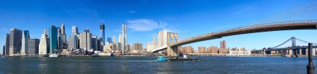 Panoramic view of Manhattan skyline and Brooklyn Bridge in New York City Фото со стока